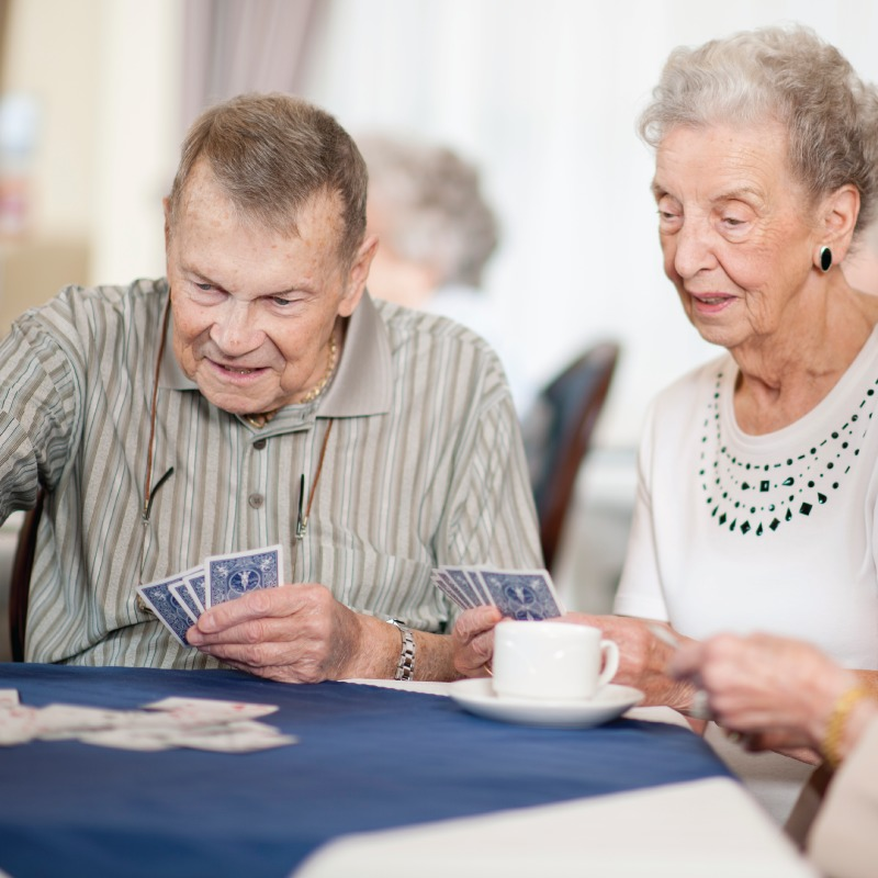 Seniors smiling and playing cards